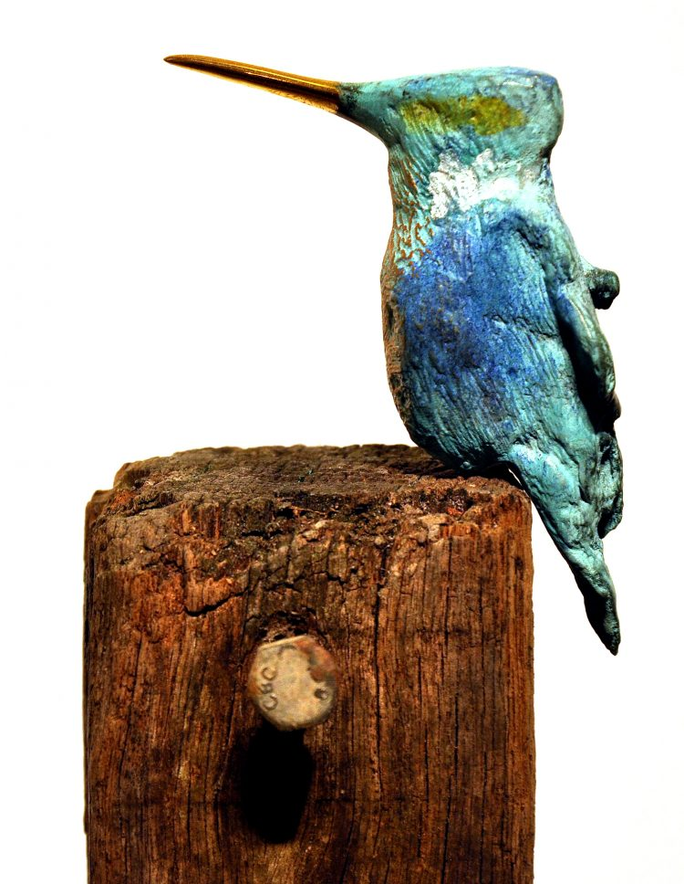 Bronzen ijsvogel op meerpaal