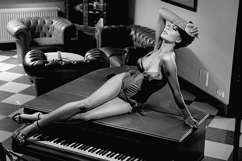 Sexy woman laying on a piano